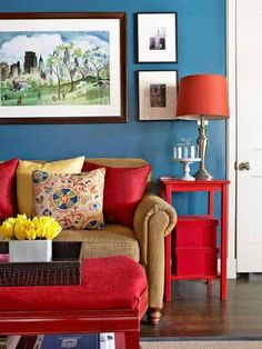 tiny-condo-interior-design-with-blue-walls-and-orange-table-lamp-shade-and-red-end-table-and-ottoman-with-tray-and-neutral-sofa-and-cushions-and-framed-pictures