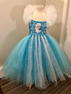 Princess Elsa inspired dress. This beautiful Elsa full length dress with off shoulder detail and long cape effect at the back . Is made on a crochet top and tulle material. The dress comes in 2 designs please leave a message as to which one you would like to purchase. The dress