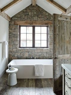Well done rustic modern bathroom. I enjoy the stacked stone wall with the heavy beams, the white stand alone tub, and the reclaimed wood floor/door.