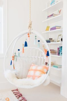 A white hanging chair accented with tassels is hung in front of styled white she. A white hanging chair accented with tassels is hung in front of styled white shelves in a stylish girl& bedroom. Cute Girls Bedrooms, Bedroom Decor For Teen Girls, Girl Bedroom Designs, Teenage Girl Bedrooms, Cute Bedroom Decor, Cute Bedroom Ideas, Room Ideas Bedroom, Stylish Bedroom, Bedroom Inspiration