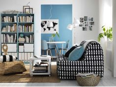 A small living room furnished with a sofa-bed for two in a black/white cover. Shown together with a white side table on castors, a modern rocking chair made of banana fibers and light turquoise bookcases.