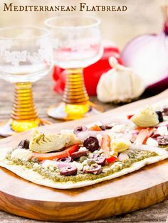 Mediterranean Flatbread is an easy to make meal or appetizer. It's loaded with pesto, artichokes, bell pepper, onion, olives and feta cheese. #SundaySupper