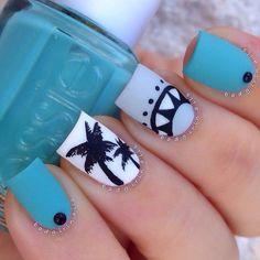 Un fresco y verano inspiraron el diseño de arte de uñas azul. Esmaltes azules azul, blanco y gris claro se utilizan como fondo con las siluetas de esmalte negro en la parte superior.