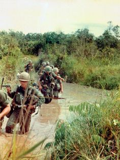 National Geographic Vietnam War | Soldiers walk through knee deep water surrounded by thick brush.