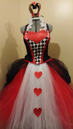 Black corset blouse with harlequinn cotton and glitter red heart. Long tulle skirt in red, tan and white with glitter heart accents Includes