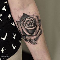 Sketchy black rose tattoo on the left forearm.
