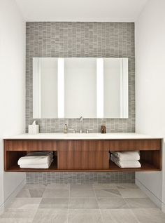 Mix up material sizes. Contrast small objects with large ones to create visual interest. This room has different shapes and sizes, from the large-format square floor tiles to the mosaic rectangular wall tiles. The wall-to-wall rectangular vanity ties them all together in a timeless, modern design.