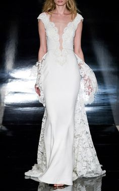This **Reem Acra** Bella gown features a deep V-neckline and a lace detail train.