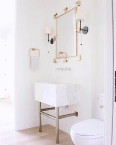 White, lucite and brass bathroom!