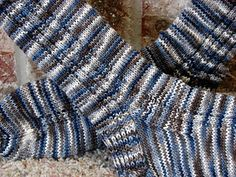 These socks are easy to knit and are a good starting point for anyone who would like to try toe-up technique for the first time. A simple Garter Rib 'tramline' climbs up both sides of each sock, adds interest and works well with plain, variegated and striped yarns..