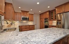 natural cherry kitchen cabinets with white granite - not sure if I like the shine on the backsplash