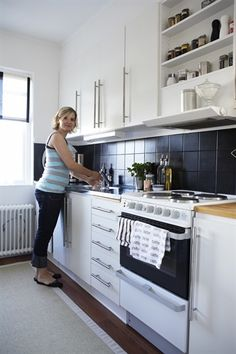 Woman stands in front of cabinets, shelves above oven to side