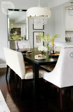 Meredith Heron - Chic dining room with Uttermost Fascination 3 Lt Hanging Shade over rectangular black dining table paired with cream tufted dining chairs and gray velvet captain chairs over cherry wood floors. Dining room features beaded beveled floor mirror and stacked art gallery.