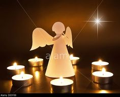 Christmas angel with candles over dark background © Preto Perola / Alamy