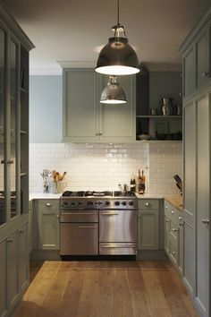 Lonny Magazine - kitchens - gray cabinets, gray cabinetry,, nickel hardware, stainless steel oven, white subway tile backsplash, cup pull hardware, butcher block counter, white counter, blue walls, nickel pendant light, under cabinet lighting,