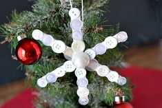 Popsicle Stick Button Snowflake- This homemade Christmas tree ornament is so fun to make, and easy to customize! This year, add this cute DIY popsicle stick button snowflake to your tree!   diy Christmas ornament, Christmas craft, homemade Christmas ornament ideas