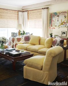 In a Hamptons summer cottage, the living room sofa is upholstered in a Manuel Canovas linen, and the table skirt and throw pillows are in Samarkand from Brunschwig & Fils to give the room a sunny feel. Click through for more of the best living room decorating ideas and designs.
