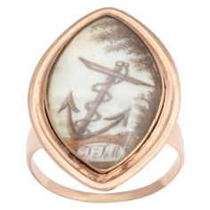 """Symbolism was everywhere in the 18th and 19th centuries. Crests and symbols on carved intaglios carried a persons trade or identity often in rebus images. The anchor was and still carries with it thoughts of hope and steadfastness. In this ring, a family chose it as a symbol to immortalize the memory of a father. On ivory in 15kt gold, is an anchor, its arrows pointed to the heavens in hope. Engraved on the reverse are the words """"In Memory of An Affectionate Father who Died in 1775. Perfect"""
