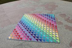 Don't Mess with my Rainbow is a half-square triangle design using solids against a grey background fabric. The colors appear in rainbow order and represent a variety of values. The quilt was finished with a concentric arcs pattern in Jacquie Gering's Craftsy course Creative Quilting with Your Walking Foot. #MidnightQuiltShow