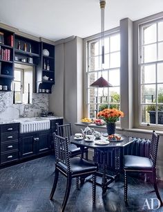 Black cabinetry complements the dark chevron floors and vintage bobbin chairs in the kitchen of fashion designer Roubi L'Roubi and Belgian financier Pierre Lagrange's London penthouse, which was designed by Veere Grenney | archdigest.com