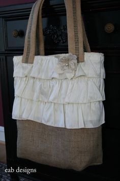 This adorable burlap tote combines the rustic elements of burlap with the elegant touch of taffeta.    Three layers of ivory taffeta ruffles surround