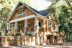 Stacked stone, giant porch, hidden garages & a deck! What a lovely craftsman home. I want it.