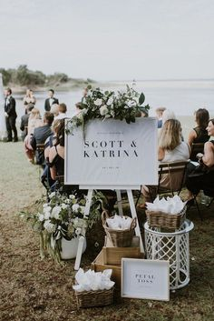 Modern romantic beach wedding ceremony welcome sign with green and white flowers and petal cones | Sarah Kennedy Photography