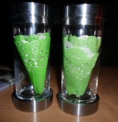 Candlesticks decorated with green doilies inside.