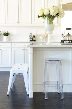 White & marble kitchen with acrylic stools