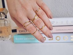 Styling by emmaengmark showing Cross Ring Gold, Victory Ring Polished Gold, Water lily Triple Zirconia Ring Gold, Wave Single Zirconia Ring Gold, Lush Pink Ring Gold and Highlight Ring Gold #jewellery #Jewelry #bangles #amulet #dogtag #medallion #choker #charms #Pendant #Earring #EarringBackPeace #EarJacket #EarSticks #Necklace #Earcuff #Bracelet #Minimal #minimalistic #ContemporaryJewellery #zirkonia #Gemstone #JewelleryStone #JewelleryDesign #CreativeJewellery #OxidizedJewellery #gold…