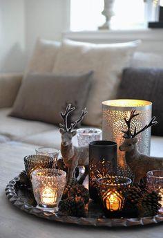 På salongbordet står et brett med små reinsdyr og levende lys og skaper julestemning i stua.