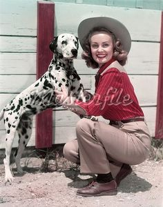 1940s 1950s SMILING WOMAN WEARING WESTERN COWGIRL OUTFIT KNEELING PETTING DALMATIAN DOG Stock Photo - Premium
