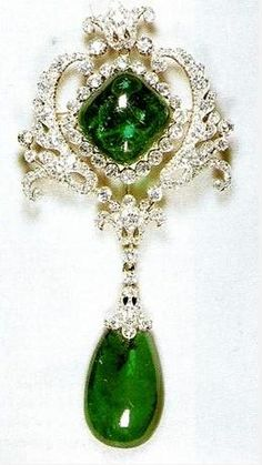 The Scroll Cambridge Emerald Brooch, part of the Personal Jewel Collection of Queen Elizabeth II, features two of the Cambridge Emeralds. Originally crafted in 1911 as part of the Delhi Durbar Stomacher, but can be detached and worn separately.