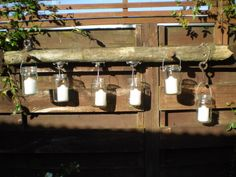 Agee and Mason jar candelabra using old fence post with barbed wire, electric fence fittings and railway spikes.