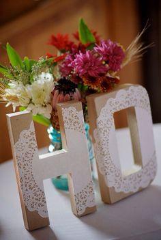 Esta novia escogio para centros de mesa poner letras con terminado en carpetas de papel.... Y frasco de vidrio de color para floreros....lindos detalles