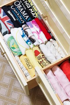 T-shirt drawers! They're labeled according to shirt style; the tops themselves are rolled rather than folded so the shirts' designs are clearly visible.