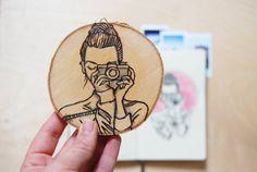 Holzscheibe mit Zeichnung einer Fotografin. Tolles Geschenk / Accessoire für die eigenen 4 Wände. Zu finden auf Etsy.