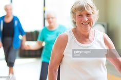 Pretty senior Caucasian woman smiles as she prepares to start line dance routine. Other senior friends are standing behind her. The woman is wearing a white work out shirt and has gray hair.
