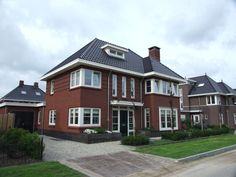 Dertiger jaren woning met rode bakstenen, witte kozijnen en zwarte pannen in Tabakssteeg, Leusden - 01 Architecten - Ontworpen door Dennis Kemper tijdens de periode dat hij bij EVE-architecten werkte.