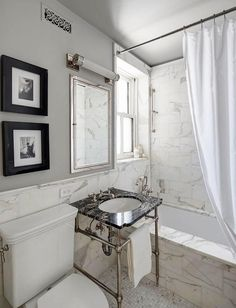 White and black bathroom features upper walls painted gray and lower walls clad in grey and white marble stacked tiles lined with stacked art over a toilet.