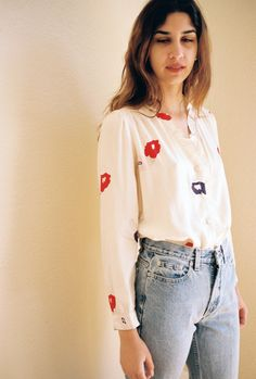 So lovely and light you'll never want to take it off. This stunning white  blouse studded with red and blue flowers is here just in time for spring  and summer. Tuck into high-waisted denim and pair with your favorite  slides. By ROLLA'S     * Materials: 50% rayon, 50% viscose     * Made in: Ch