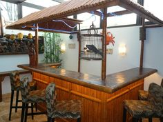 The tiki hut bar is designed with bamboo and Chinese antiques. Who knew that a fish would make a great accessory in the cage?