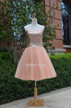 Haut de la robe est fait de champagne paillette avec une encolure damoureux.    La jupe est faite de couches de tulle rose rose.    Ce genou longueur