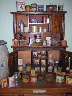 "Salesman Sample Tins displayed on a Oak Toy Cupboard (it is 18"" tall for reference)"