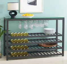 """Tag Furnishings 290089 Trio Wide Table Wine Rack, Black by Tag. $685.00. This item ships common carrier.. Sturdy construction made from 1.5"""" mild steel tubes. For slatted shelves holds as many as 64 bottles. Color: Black / Clear. Size: 36""""H x 54""""W x 17.75""""D. Finish:Black Trio wide table & wine rack.   Sturdy construction frameutilizing 1' square mild steel tubes  Glass top is 3/8' thick  Top rack holds as many as 32 stems  Four slatted shelves holds as many as 64 bottles ..."""