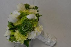 Classic white and green bridal bouquet with hydrangea, succulents, freesia, and tulips. Fleurish Floral Designs