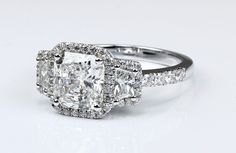 Sparkle, everywhere! This gorgeous Radiant cut diamond engagement ring features two unique Trapezoid-shape side diamonds surrounded by fiery pave halo, with larger diamonds lining the shank. Mounted in Platinum.