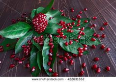 pomegranate seeds lie on green leaves - stock photo