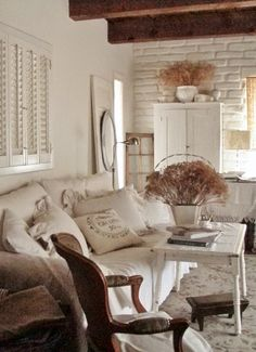 Neutral farmhouse French style ♥ this room! dried flowers, chippy white table, grainsack pillow, painted brick, louvered blinds Cottage and Cabin blog