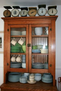 scales, beadboard in back of cabinet, wood, and dishes.
